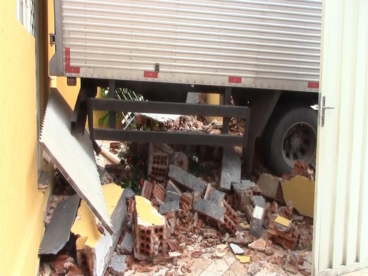 Caminhão atinge casa e destrói muro