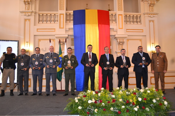 Autoridades da área de segurança pública recebem o troféu.