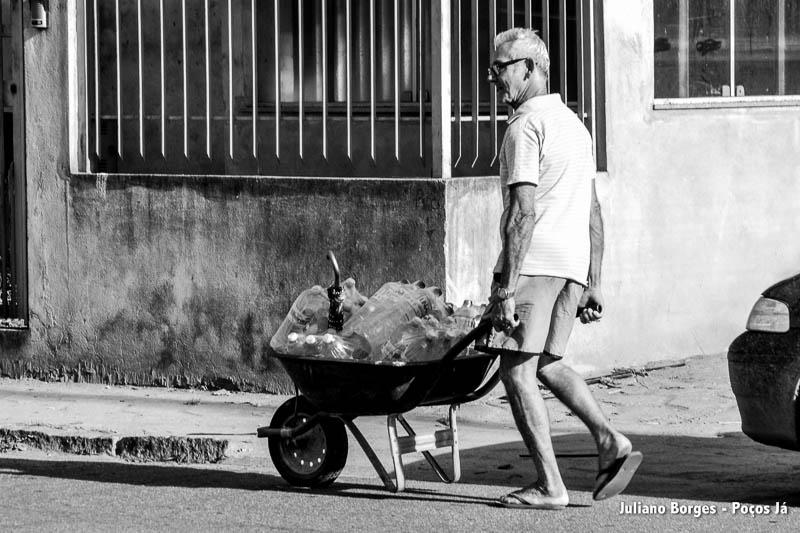 Senhor carrega carrinho de mão cheio de garrafas d'água.