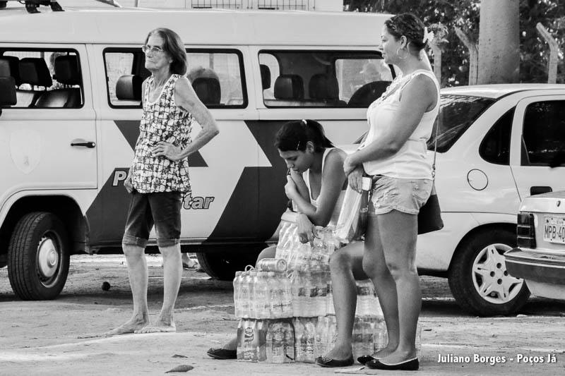 No Centro, moradores passam várias vezes pela fila para pegar água.